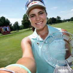 Lexi Thompson takes a simulated selfie with the championship trophy after winning the Meijer LPGA Classic presented by Kraft at Blythefield Country Club on Sunday, July 26, 2015, in Grand Rapids, Michigan.