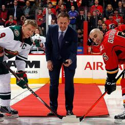 Gary Roberts (center) participates in a ceremonial puck drop before the Calgary Flames and the Minnesota Wild face off at Scotiabank Saddledome.