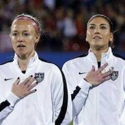 United States' Becky Sauerbrunn, left, and Hope Solo, right, stand during the playing of the national anthem before the team's CONCACAF Olympic qualifying tournament soccer match against Costa Rica on Wednesday, Feb. 10, 2016, in Frisco, Texas. (AP Photo/