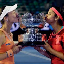 Martina Hingis, left, of Switzerland and Sania Mirza of India kiss their trophy after defeating Czech Republic's Andrea Hlavackova and Lucie Hradecka in the women's doubles final at the Australian Open tennis championships in Melbourne, Australia, Friday,