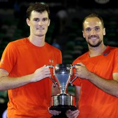 Jamie Murray, left, of Britain and Bruno Soares of Brazil hold their trophy after defeating Daniel Nestor of Canada and Radek Stepanek of the Czech Republic in the men's doubles final at the Australian Open tennis championships in Melbourne, Australia, ea