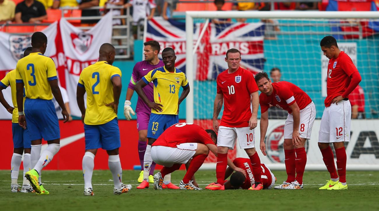 Concerned England players check on injured Alex Oxlade-Chamberlain during a pre-World Cup 2-2 draw with Ecuador.