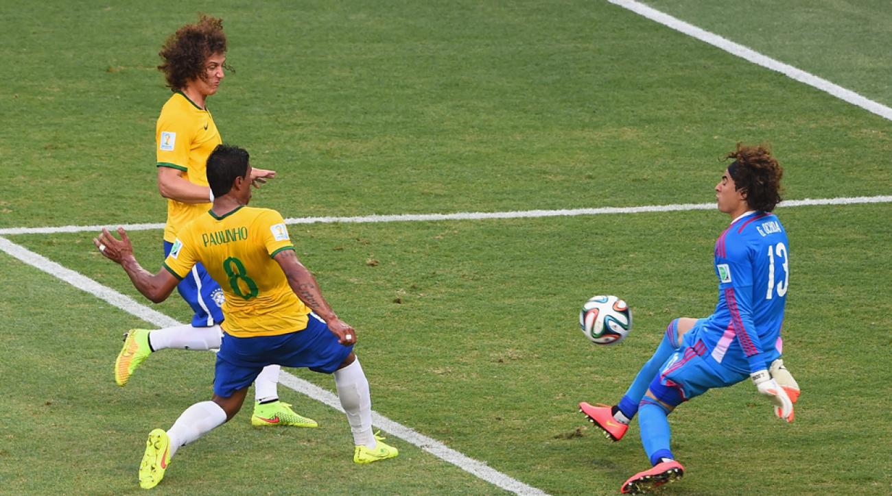 Mexico goalkeeper Guillermo Ochoa comes up huge to rob Paulinho, with David Luiz lingering on the doorstep, in the first half of Mexico's clash with Brazil on Tuesday.