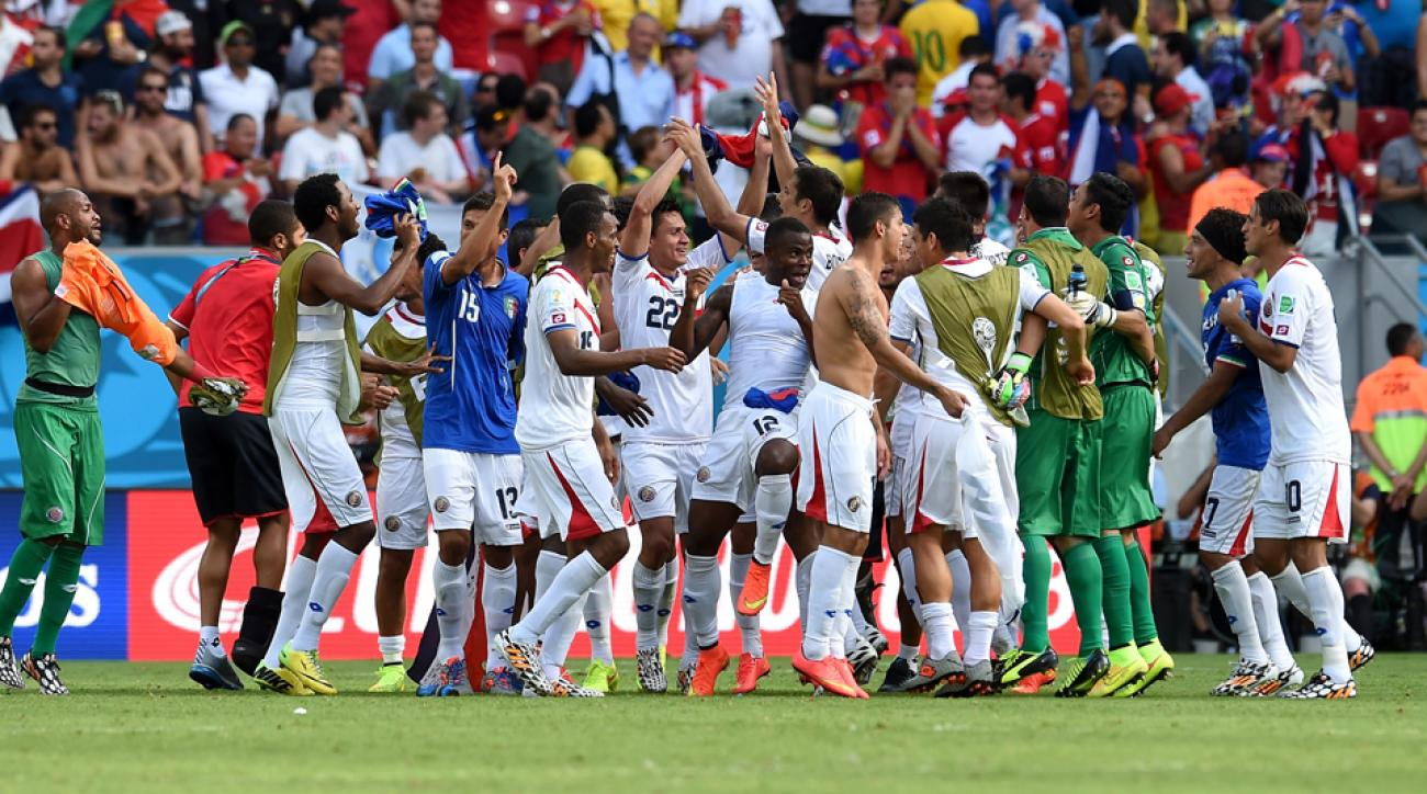 Costa Rica players soak in a 1-0 win over Italy, which sealed their place in the World Cup's knockout stage.