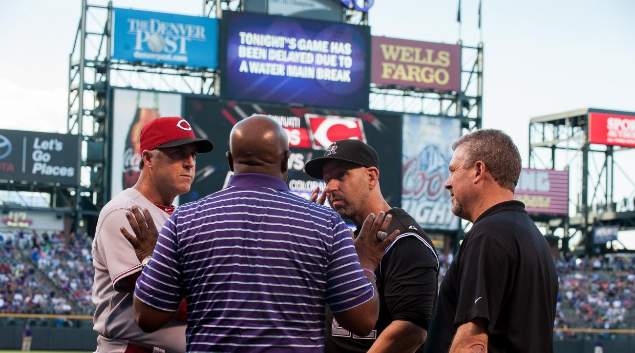 Officials from both teams gather to discuss the decision to postpone the match-up after a water main break outside Coors Field.
