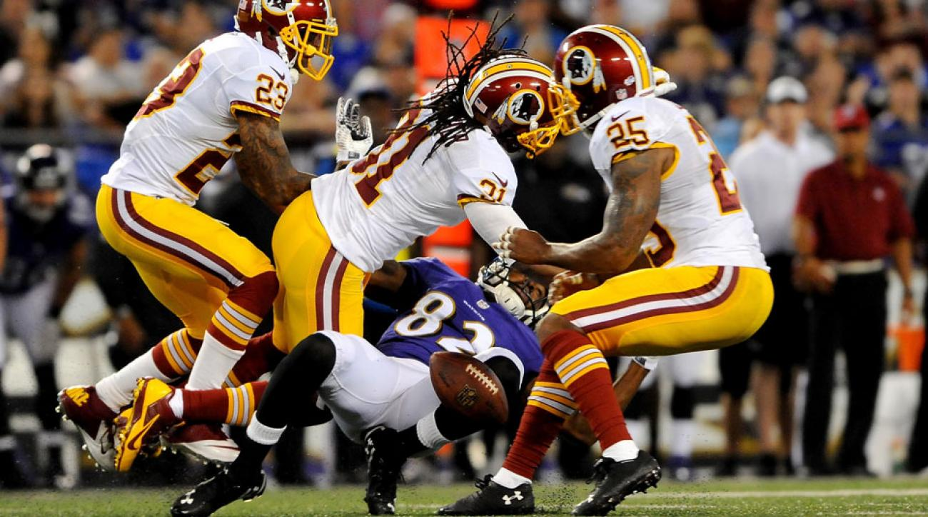 The Ravens' Torrey Smith gets hit by Washington safety Brandon Meriweather during Saturday's preseason game