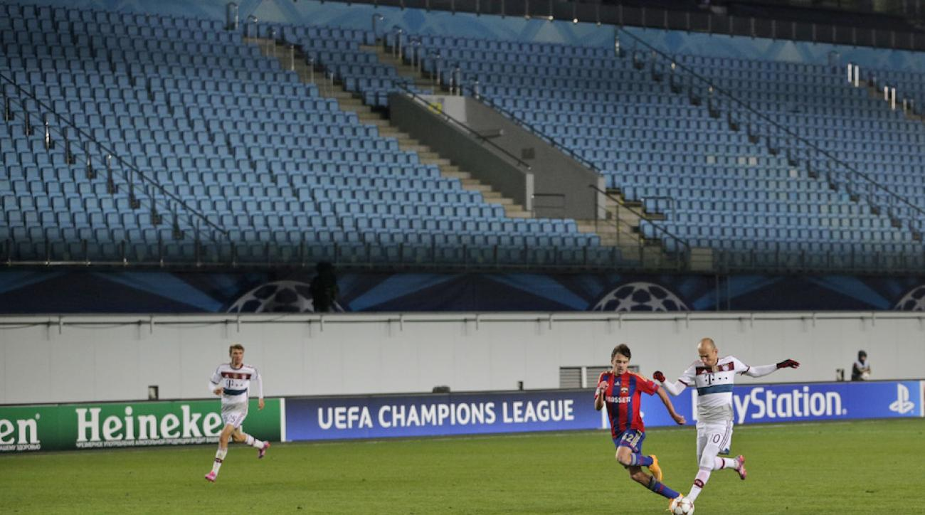 CSKA's Georgi Schennikov, center left, and Bayern's Arjen Robben, center right, vie for the ball in a stadium devoid of fans during a Champions League match