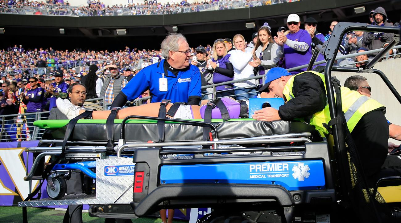 A Ravens cheerleader is taken off the field after falling while performing during a game between the Baltimore Ravens and Tennessee Titans on November 9, 2014.