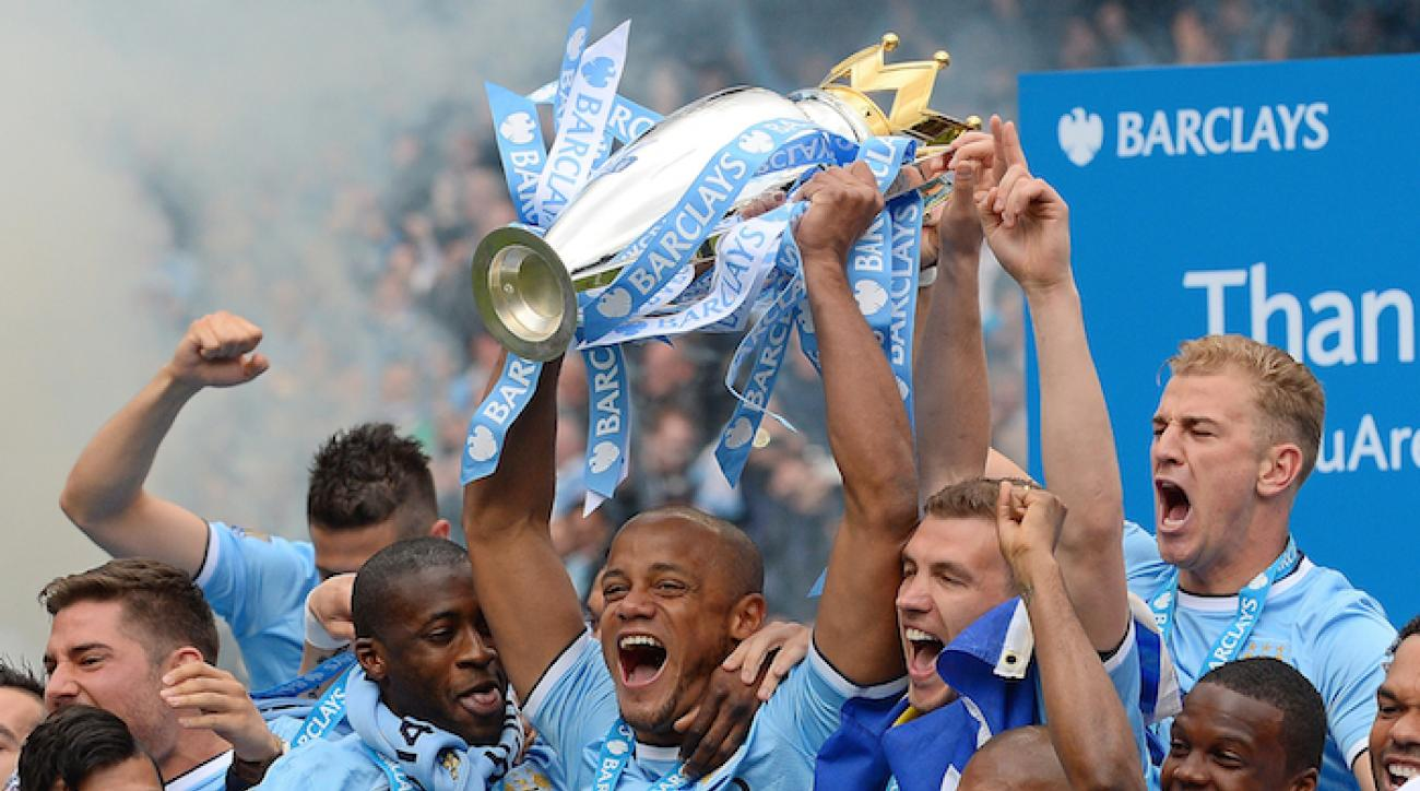 Manchester City's Belgian midfielder Vincent Kompany (C) celebrates with the Premiership trophy after his team won 2-0 during the English Premier League football match between Manchester City and West Ham United at the Etihad Stadium in Manchester on May 11, 2014.