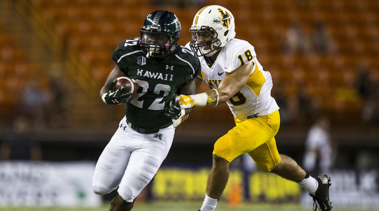 Diocemy Saint Juste #22 of the Hawaii Warriors is defended by Xavier Lewis #18 of the Wyoming Cowboys while carrying the ball during the fourth quarter of a college football game between the Wyoming Cowboys and the Hawaii Warriors at Aloha Stadium on October 11, 2014 in Honolulu, Hawaii.