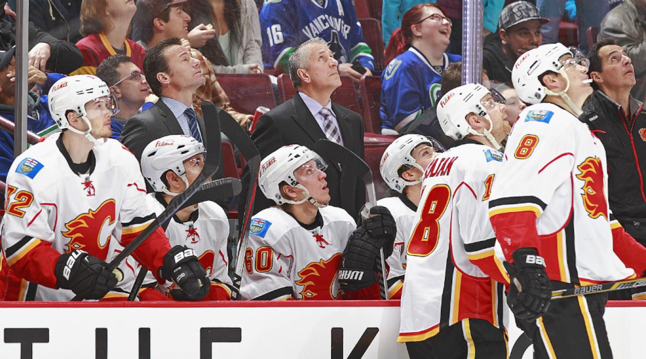 The Flames bench watches the replay of their own goal against the Canucks.