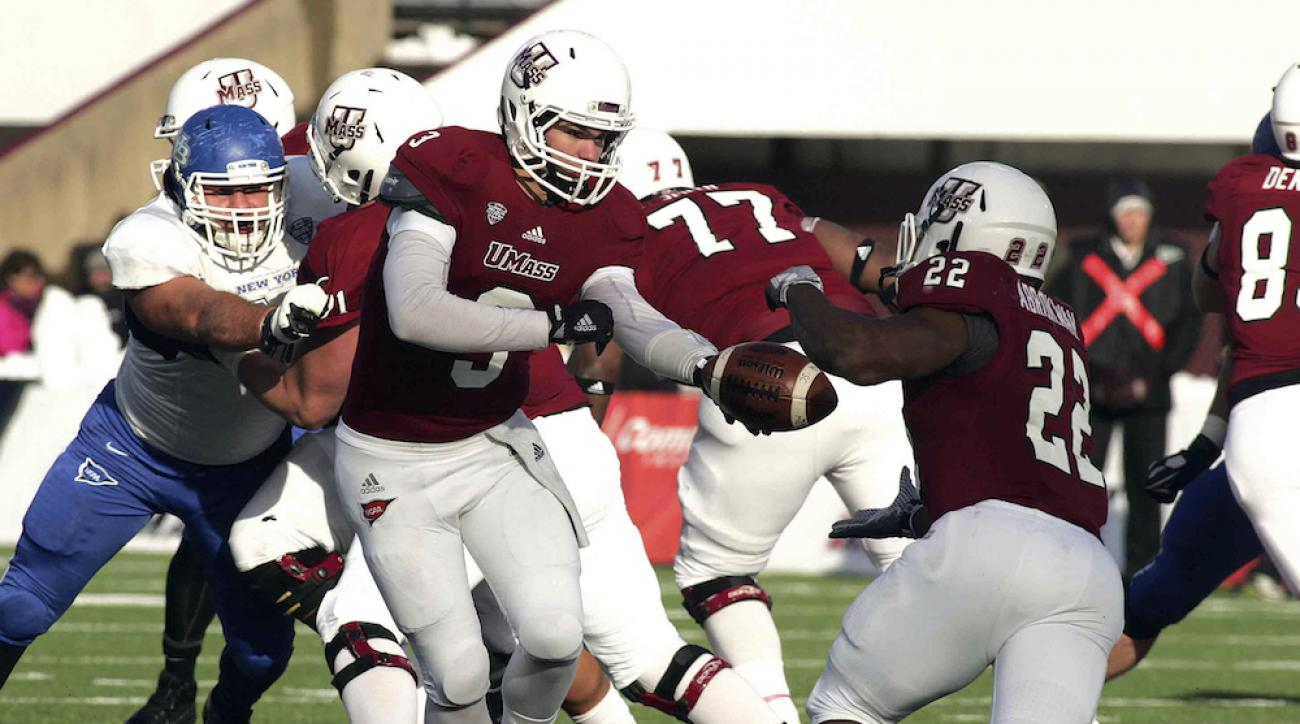 UMass quarterback Austin Whipple hands the ball off to running back Shadrach Abrokwah in a game against Buffalo on Nov. 28, 2014.