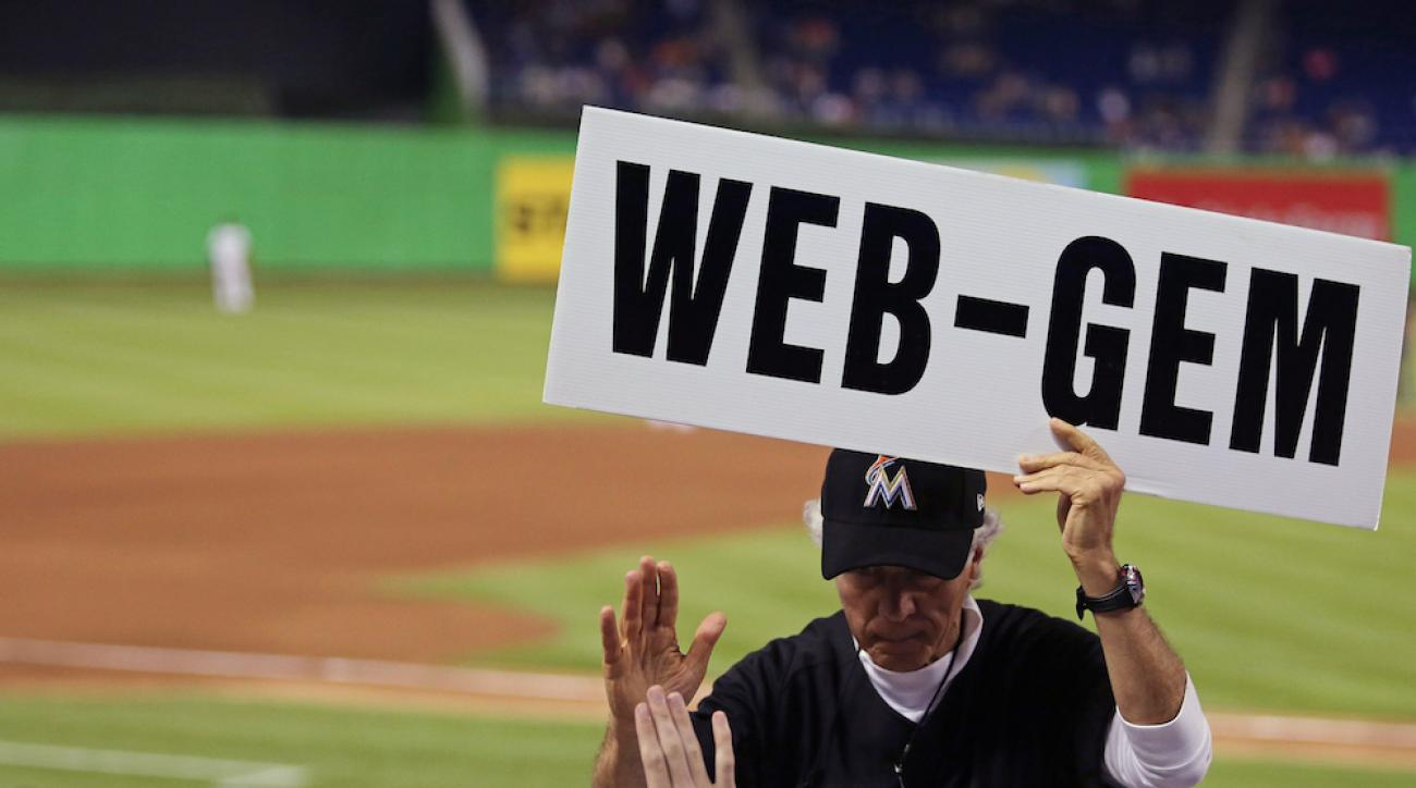 """A Marlins fan holds up a """"Web-gem"""" sign after Giancarlo Stanton made a diving catch in the fourth inning of Wednesday's game against the Braves."""