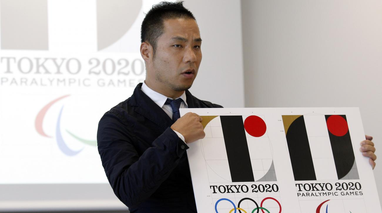 Japanese designer Kenjiro Sano gives a detailed explanation of how he came up with his logo, left, for the 2020 Tokyo Olympics at a press conference in Tokyo in August.