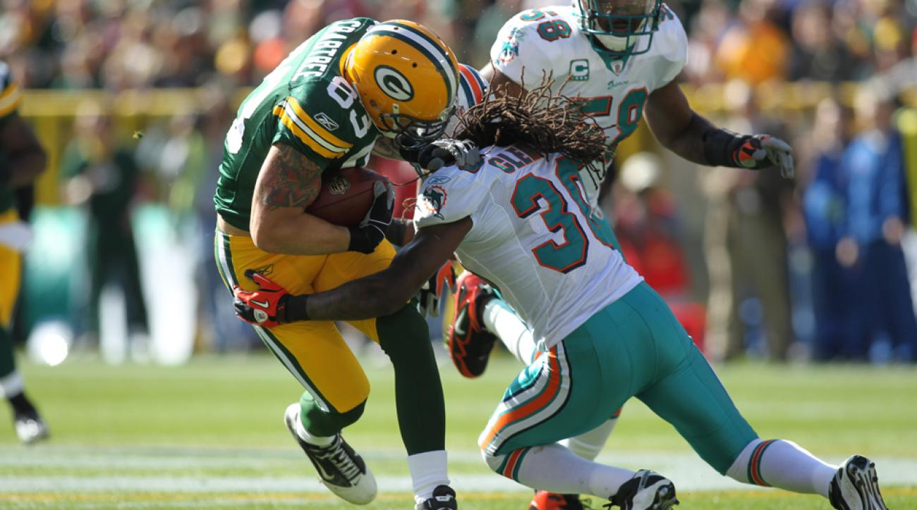 Tom Crabtree is hit by Chris Clemons of the Miami Dolphins during a game in 2010
