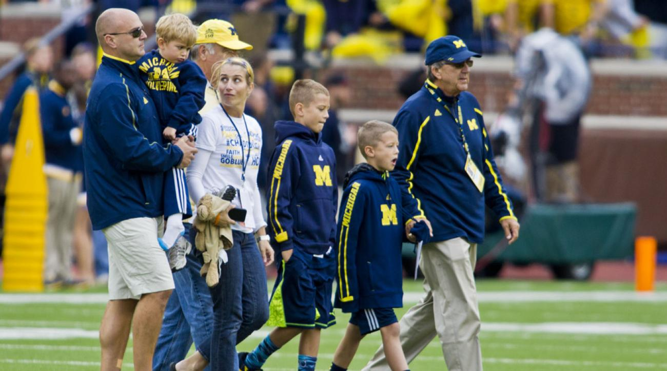 Former Michigan coach Lloyd Car leads his family onto the Michigan Stadium field for the pregame coin toss before a game against Oregon State