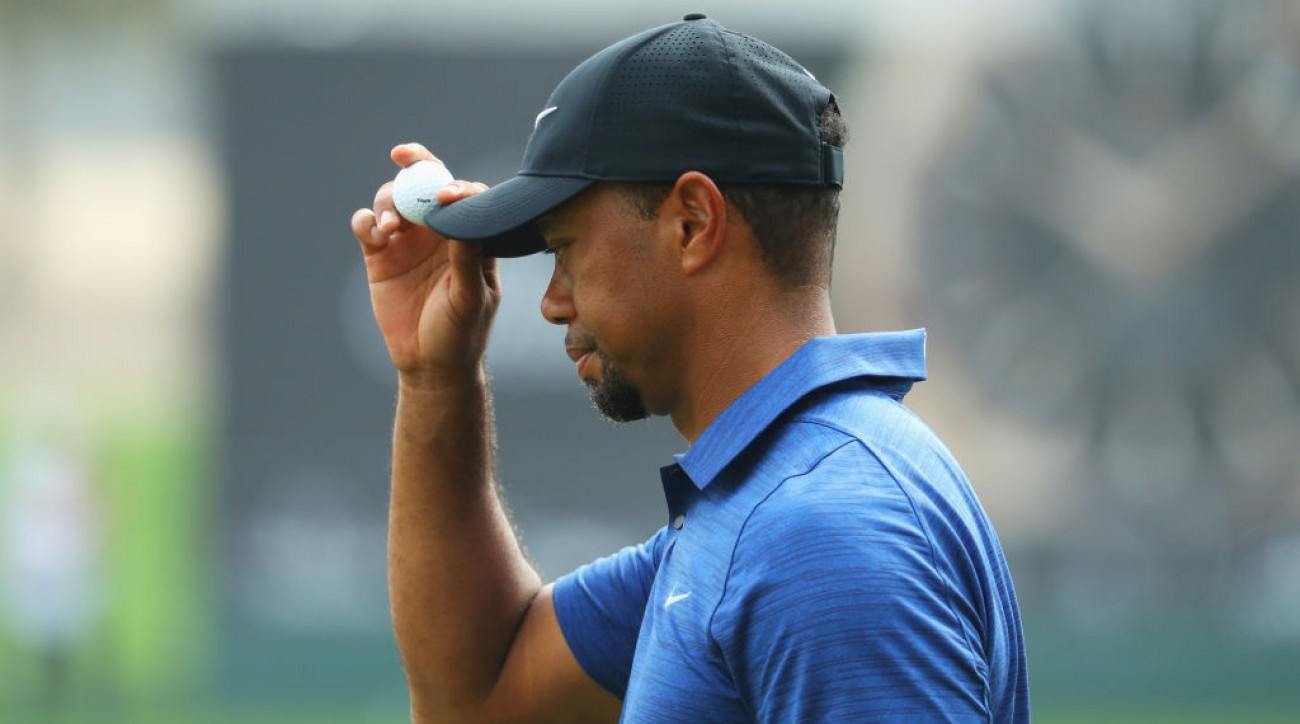 Tiger Woods acknowledges the crowd on the 9th green during the first round of the Omega Dubai Desert Classic.