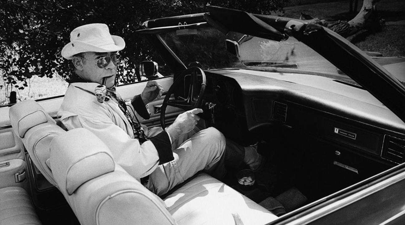 Writer & journalist Hunter S. Thompson photographed driving a convertible.