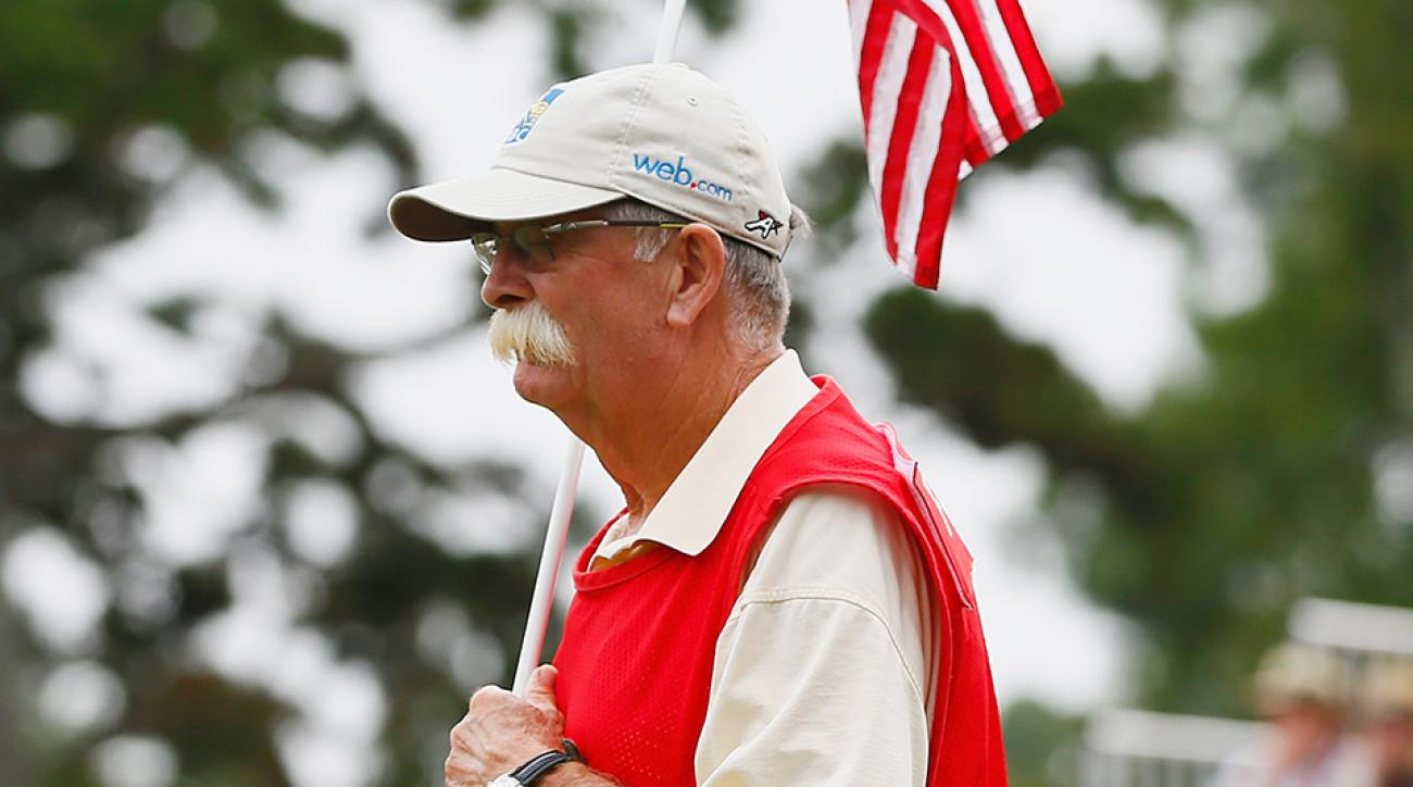 "Caddie Mike ""Fluff"" Cowan waits on the 16th green during the final round of the 2014 Tour Championship."