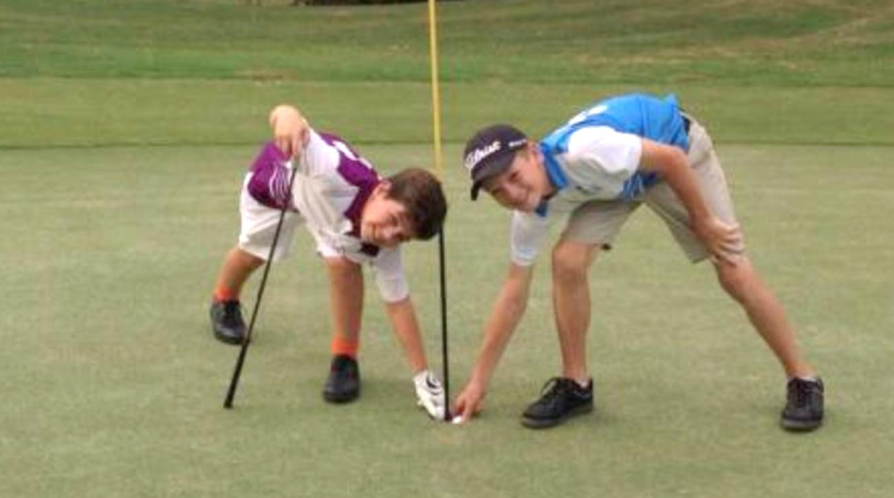 John Berrigan (left) and Harrison Mancill reach down to claim their hole-in-one balls.