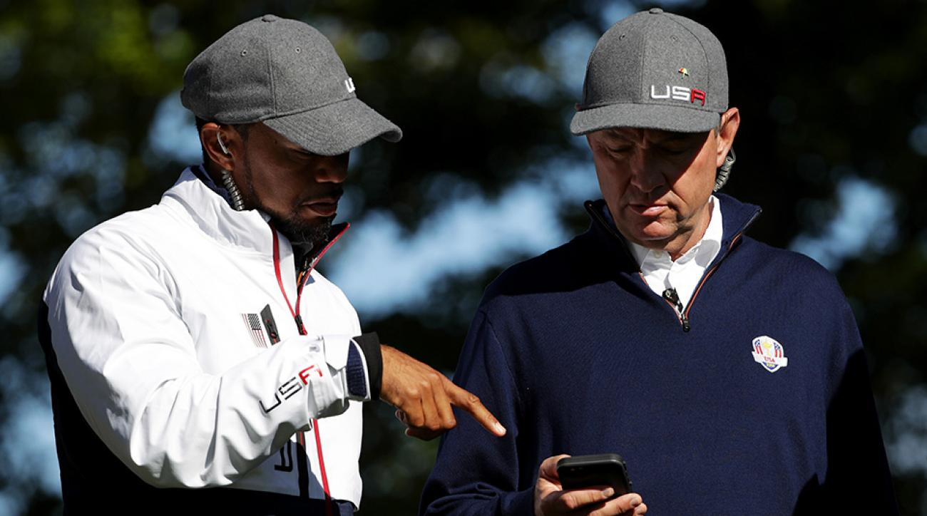 Vice captain Tiger Woods and captain Davis Love III talk during Saturday morning foursome matches of the 2016 Ryder Cup at Hazeltine National Golf Club.