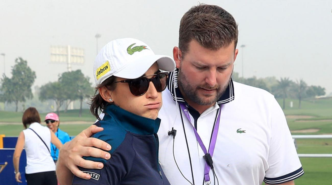 Anne-Lise Caudal is consoled by tournament director Michael Wood after her caddie collapsed on the course.