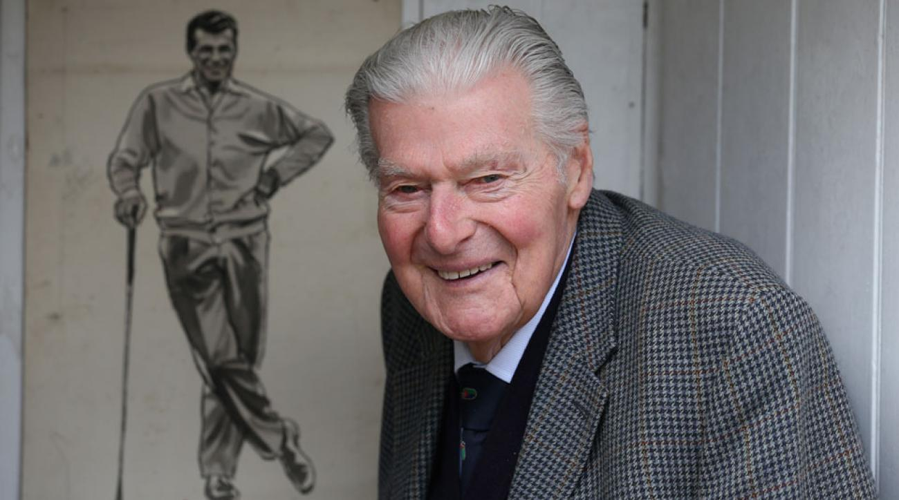 John Jacobs poses for a photograph next to a charcoal drawing of himself at his home in England in 2013.