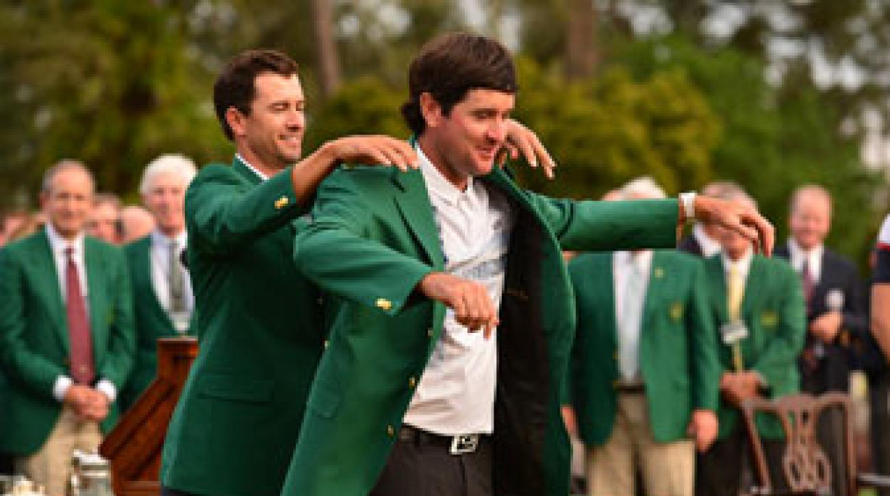 Bubba Watson slips into his second green jacket with some help from Adam Scott.