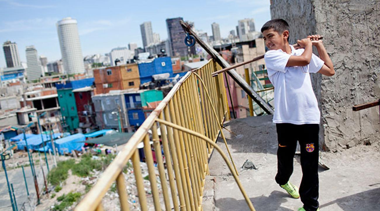 Dylan Reales poses on the terrace of his home in Buenos Aires with his first club, fashioned from a broken broomstick.