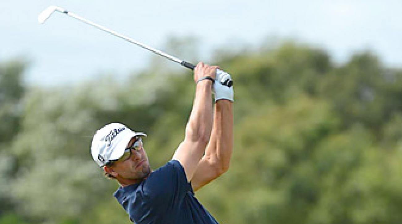 Adam Scott matched a course record at Lytham with a six-under 64.