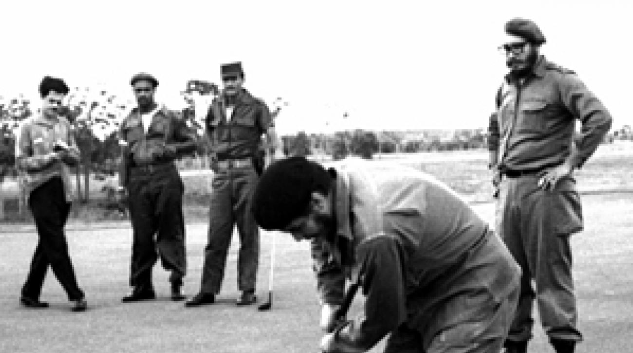 Che Guevara putts as Fidel Castro looks on in 1961.
