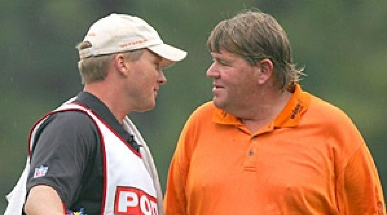 After ducking into a Hooters hospitality tent during the rain delay, John Daly emerged with Tampa Bay Buccaneers Coach Jon Gruden as his caddie.