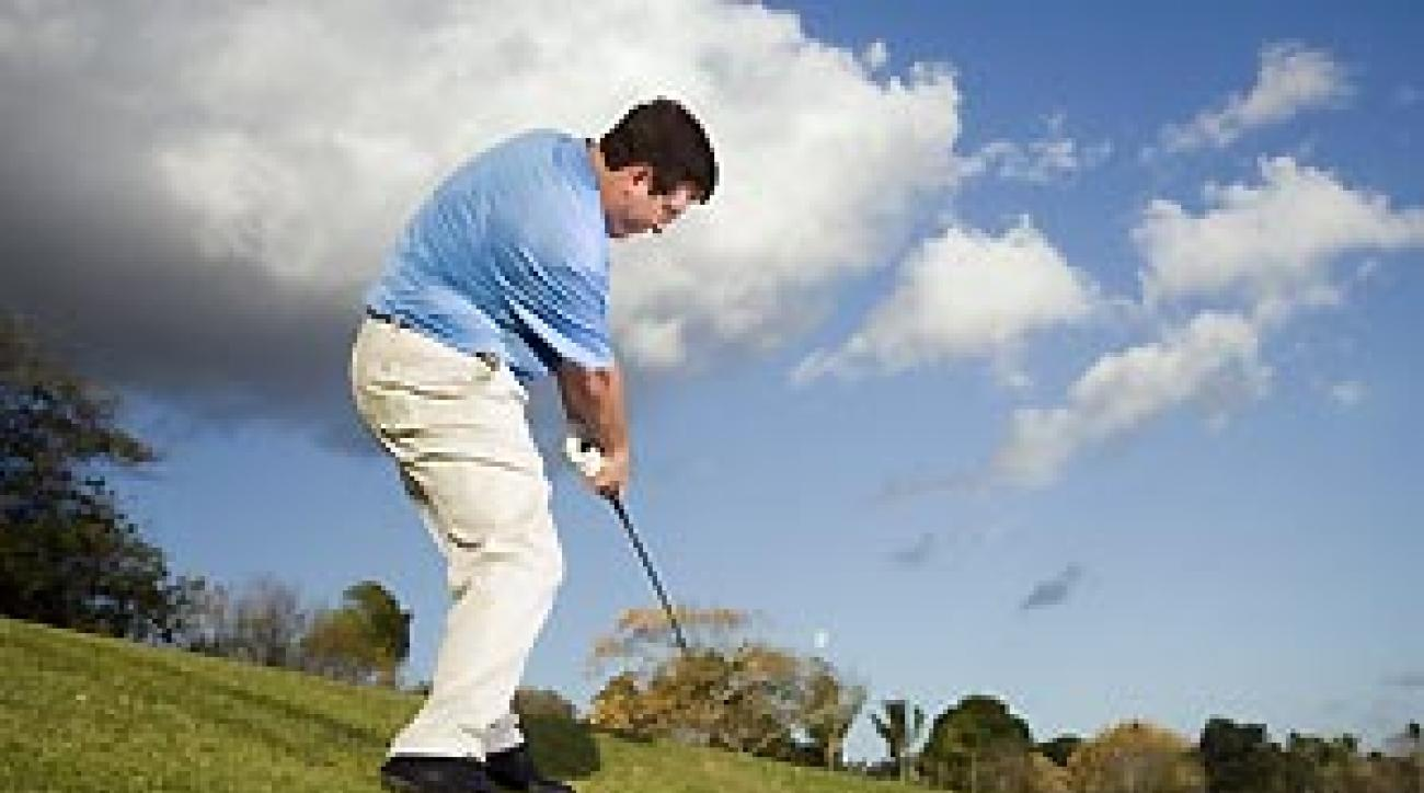 Take a wider stance and add more knee flex to lower your body and bring you closer to the ball.