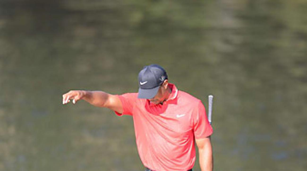 Tiger Woods took a drop on the 14th hole after hitting his tee shot into the water. He went on to make a double bogey.