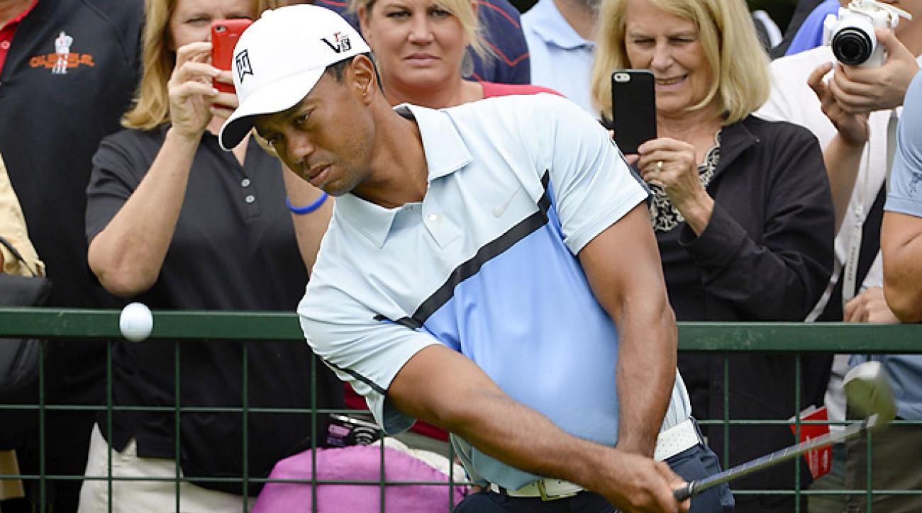 Tiger Woods, shown here practicing at East Lake, wants to see changes in how fans can phone in and affect the outcome of golf tournaments.