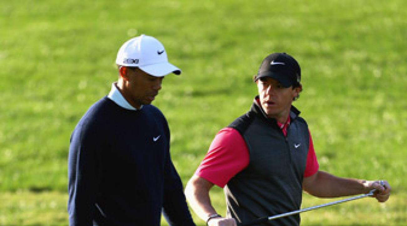 Tiger Woods, left, and Rory McIlroy struggled on Thursday in Abu Dhabi.