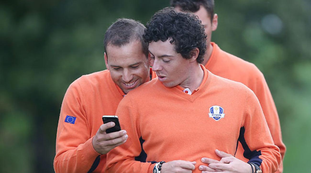 Sergio Garcia and Rory McIlroy check out a smartphone at the 2012 Ryder Cup at Medinah.