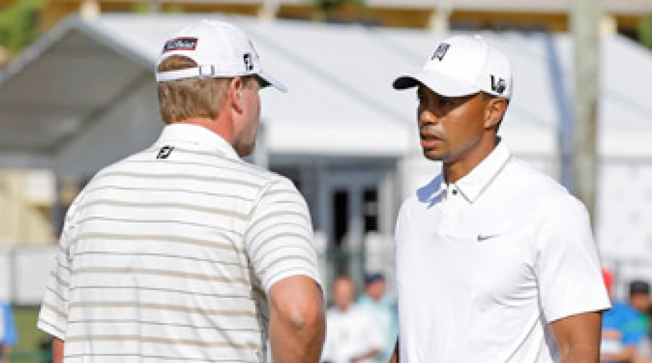 Steve Stricker talks with Tiger Woods on the practice putting green at Doral Wednesday.