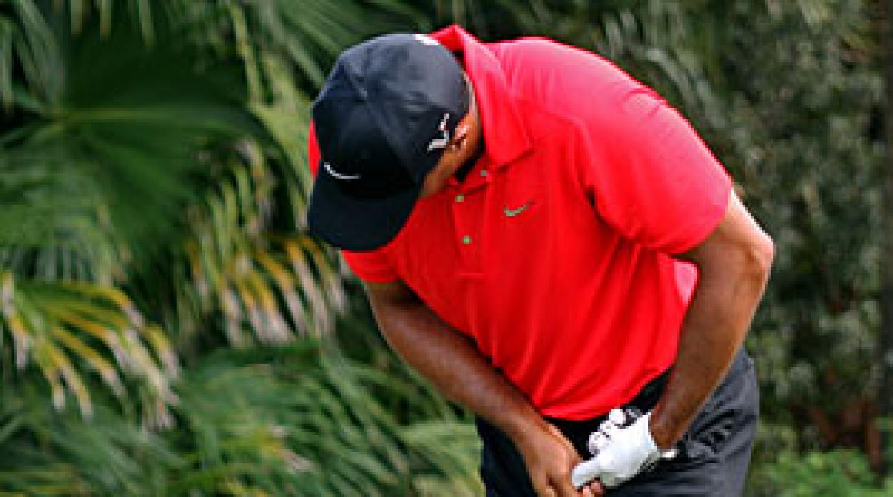 Tiger Woods grimaced after hitting his drive on No. 12 and then withdrew from the tournament.