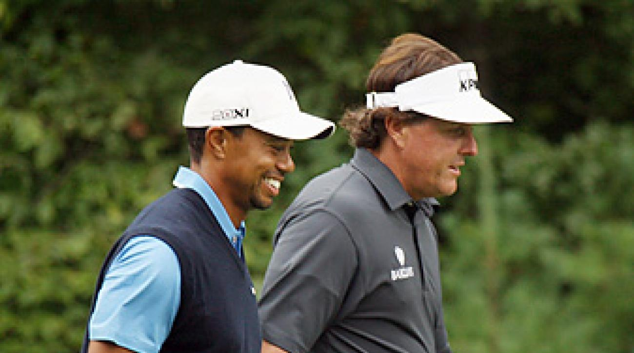 Tiger Woods and Phil Mickelson walk along the 13th fairway during the opening round of the 2013 Deutsche Bank Championship at TPC Boston.