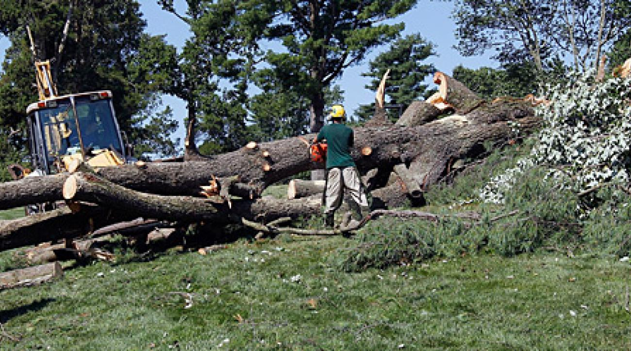Workers cut up a tree along the 14th fairway after an overnight storm caused massive damage at Congressional.
