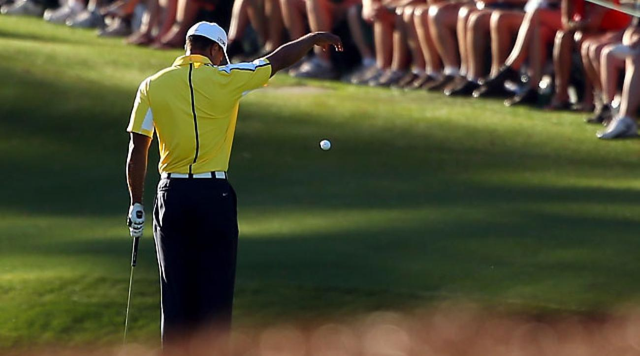 Tiger Woods drops his ball after he hits it into the water on the 15th hole during the second round of the 2013 Masters.