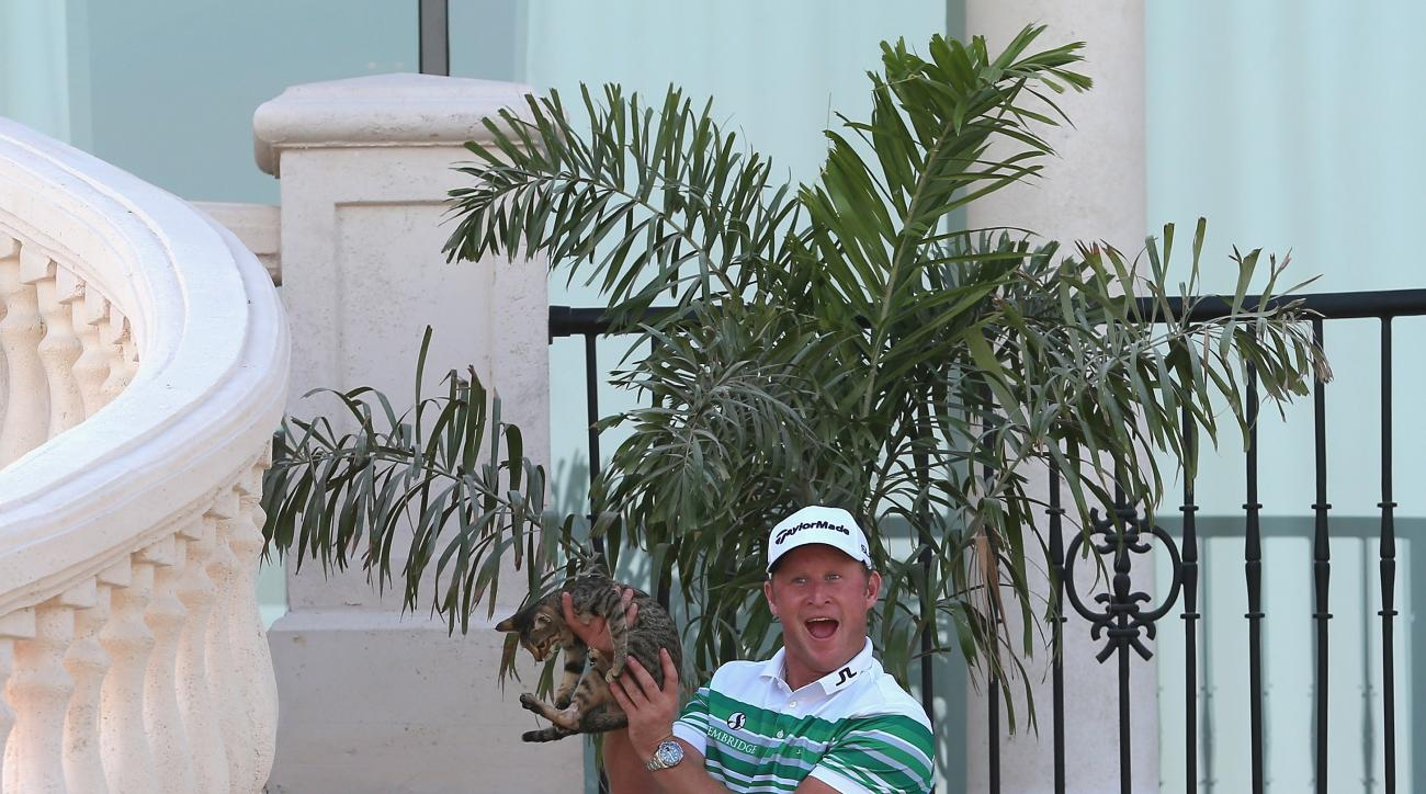 Jamie Donaldson poses with a cat he retrieved from a precarious flower bed during the third round of the DP World Tour Championship at Jumeirah Golf Estates.