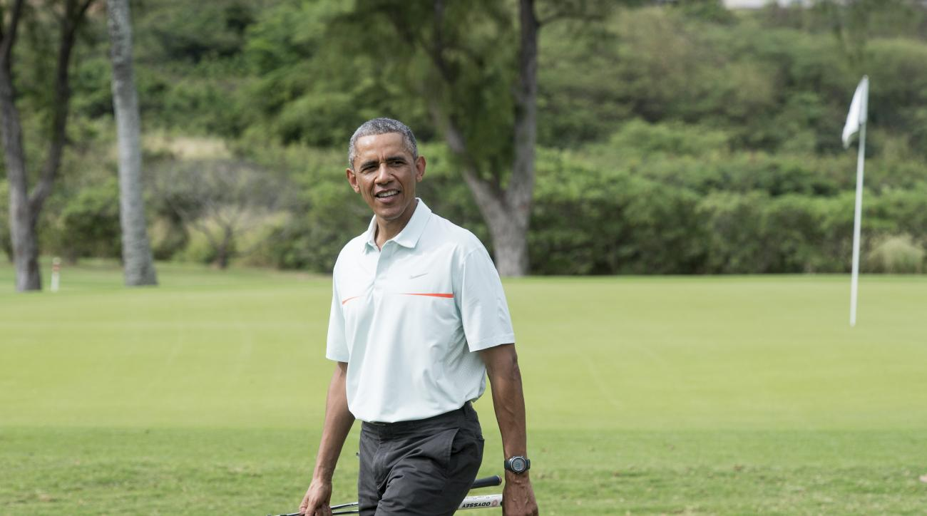 President Barack Obama talks to reporters as he plays golf with Malaysian Prime Minister Najib Razzak.