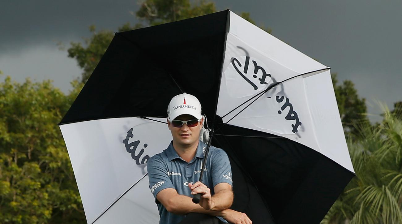 Zach Johnson waits under an umbrella on the tenth tee during the second round of the Hero World Challenge at the Isleworth Golf & Country Club on December 5, 2014