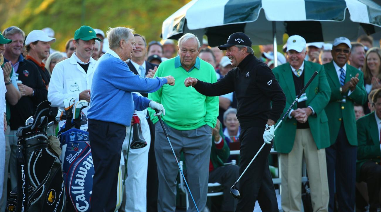 Jack Nicklaus and Gary Player fist-bump as Arnold Palmer looks on at the ceremonial opening tee shot at the 2014 Masters.