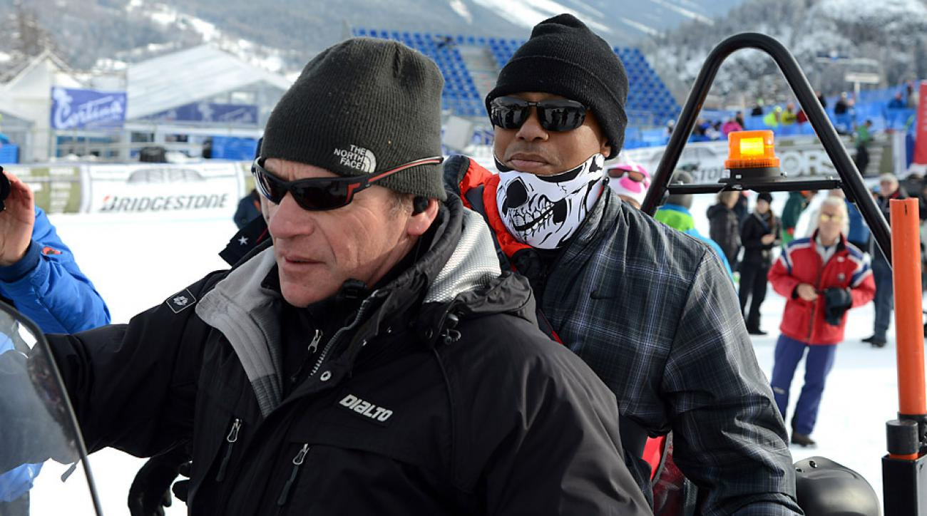 Tiger Woods, right, leaves the finish area of an alpine ski, women's World Cup super-G, in Cortina d'Ampezzo, Italy. Lindsey Vonn won a super-G Monday for her record 63rd World Cup victory