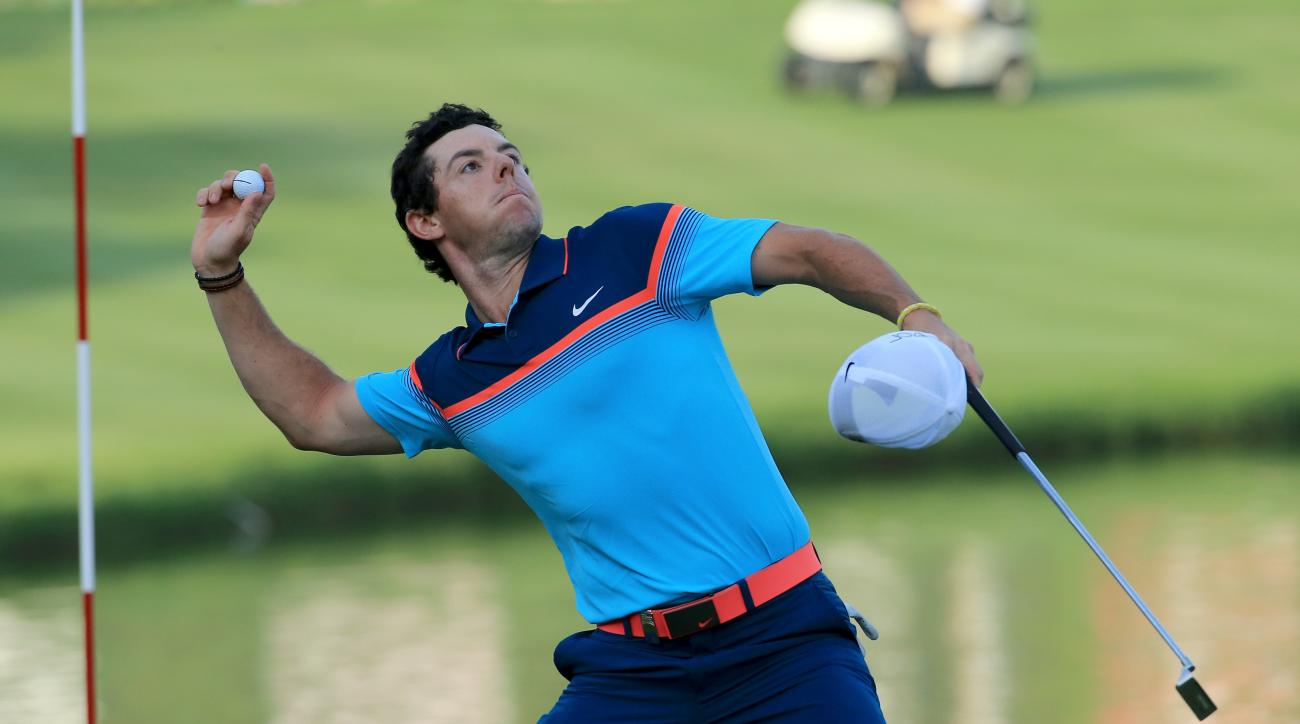 Rory McIlroy throws his ball into the crowd after holing out on the 18th green to win the 2015 Dubai Desert Classic.