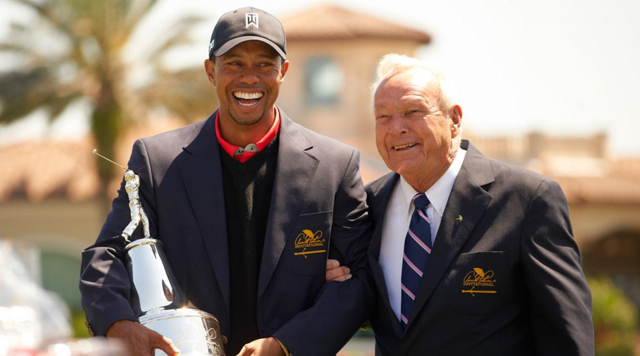 Tiger Woods laughs with Arnold Palmer while holding the trophy after winning the Arnold Palmer Invitational in 2013.