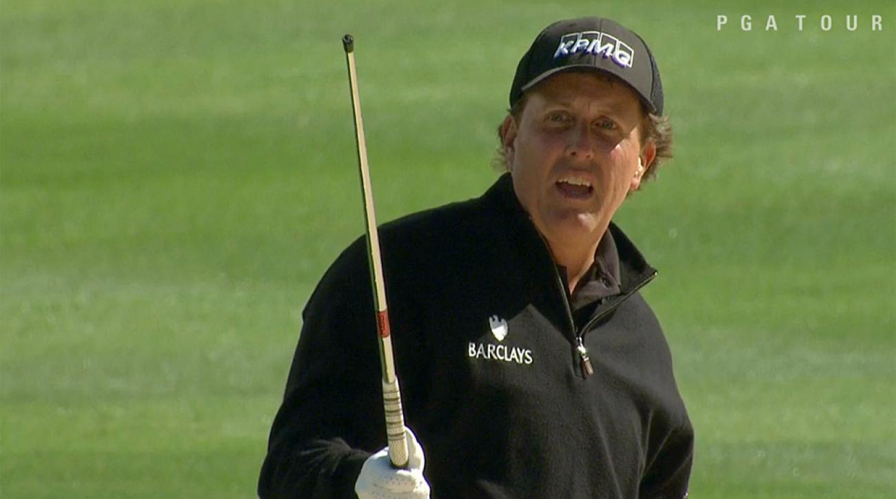 Phil Mickelson stares in disbelief at his headless iron shaft.